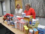 Our Advent party showing the food pantry donations with two members (Jeannette Brochu and Mary Ainsworth) who are on the board for the food pantry.